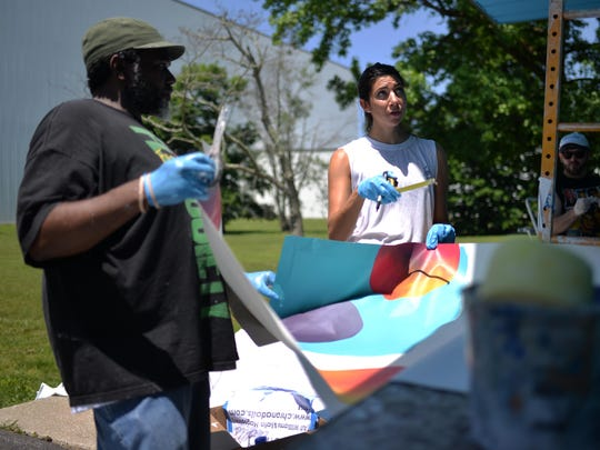 Artist Ali Williams (right), of Chroma Dolls fine art collective, and Randy Bullock (left), both of Philadelphia, install a mural on the Boys and Girls Club of Vineland building Tuesday, Jun. 7 in Vineland.