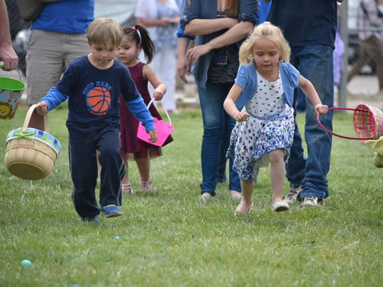 Atticus Faber, 4, and Sara Banta, 4, rush to find treasure at the annual Yerington Lions Club Easter Egg Hunt at the Yerington High School athletic fields Sunday.