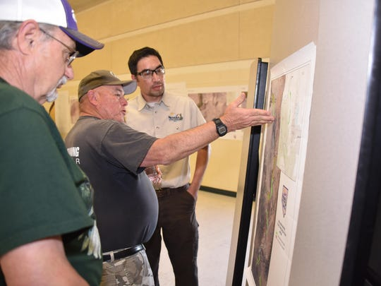 Nevada Division of State Parks Northern Region manager Dale Conner provides an explanation to Yerington resident Wes Allan, center, at the public workshop on the proposed Walker River State Recreation Area on April 19 in Yerington.