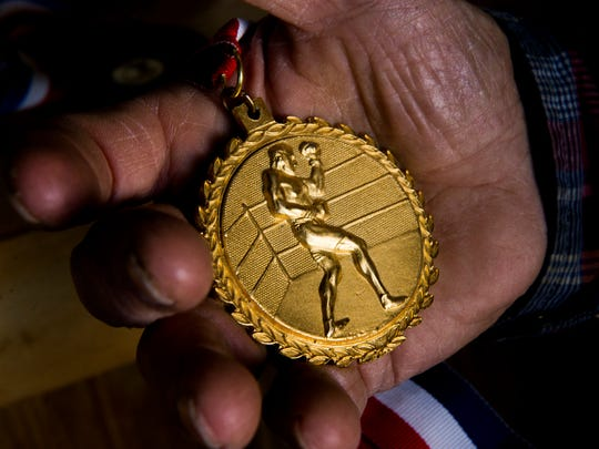 Neely Owens holds a boxing medal found inside a folded American flag in Paris, Tennessee on October 26, 2017.