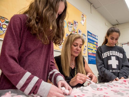 River Dell Middle School teacher Miriam Gargiulo demonstrates how to knot fleece blankets to members of her seventh grade homeroom class on Tuesday December 19, 2017.