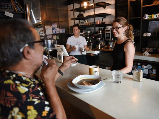 Deveri Gifford, right, co-owner of Brooklyn Street Local, speaks with Raphael Rivera. She said she hopes Corktown keeps its close ties.