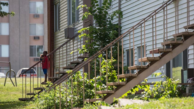 A child stands on the stairs outside of the River Hills Apartments on Tuesday, June 20, 2017, in the East Village.