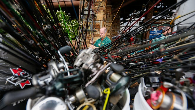 Bass Pro Shops employee Kevin Williams sets out fishing rods outside the front entrance of the store on Thursday, June 7, 2018. Bass Pro Shops and Cabela's are donating 50,000 rods and reels to nonprofit organizations to help children connect with the outdoors.