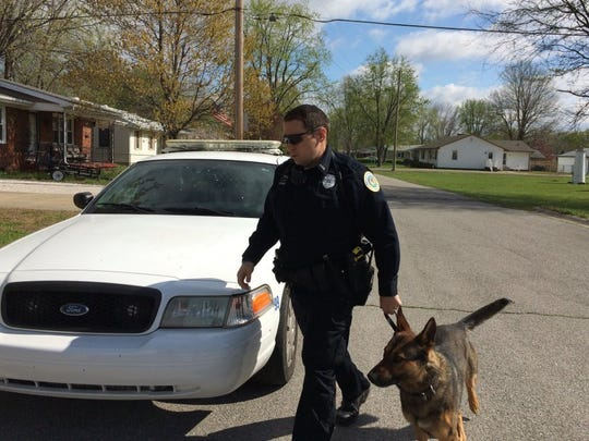 Beth Smith / The Gleaner Henderson Police K-9 Officer Kyle Stone and Exo approach a house on Sutton Drive during a drug raid early Thursday dubbed Operation Spring Cleaning.