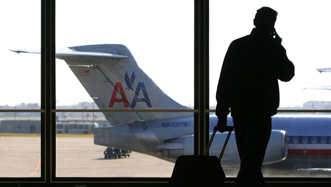 FILE- A traveler talks on his cell phone as he walks past a parked American Airlines jet awaiting its departure from O'Hare International Airport in Chicago.