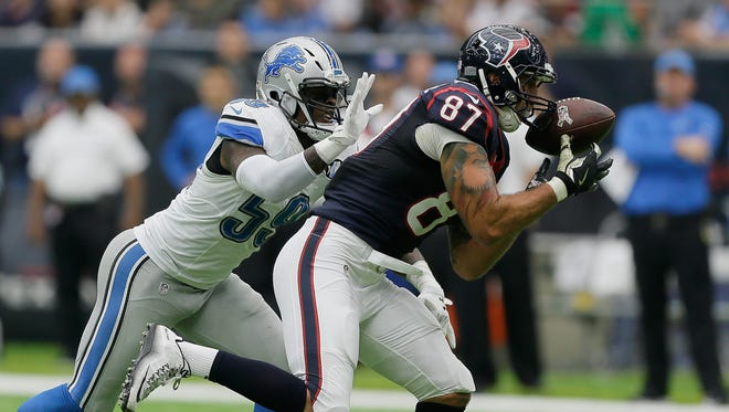 C.J. Fiedorowicz of the Houston Texans makes a catch as Tahir Whitehead of the Detroit Lions attempts to make a tackle Oct. 30, 2016 in Houston.