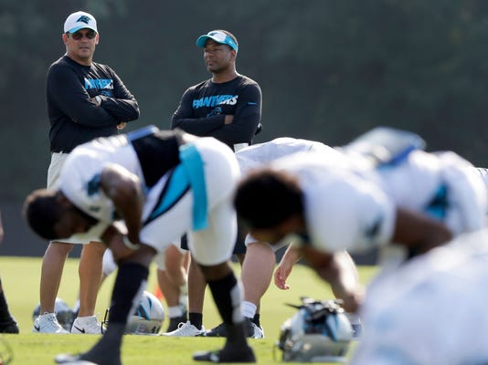 Carolina Panthers head coach Ron Rivera, left, talks with assistant head coach Steve Wilks, right, as players warm up during the NFL football team's training camp in Spartanburg, S.C., Monday, Aug. 3, 2015. (AP Photo/Chuck Burton)