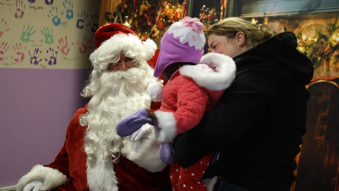 Erin Eckert, 37, holds Alexis Exckert, 1, both of Endwell, as Alexis meets Santa during Christmas in the Park.