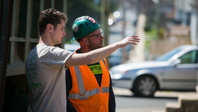 Brennan Stark, CEO and co-founder of Y Innovations, chats with a construction worker at a long-abandoned site on the 2900 block of North Jefferson Street in Wilmington, where Y Innovations is building a straw home for low-income families through Family Promise.