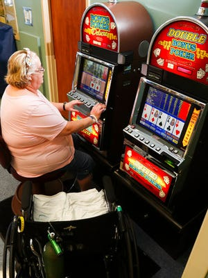 In this Thursday, March 9, 2017, photo, Angela Ingerson plays a poker slot machine as part of cognitive and physical rehab for patients at the HealthSouth Rehabilitation Hospital of Henderson in Henderson, Nev. Video poker machines are commonplace in Las Vegas and can be found in bars, supermarkets and even high-end restaurants. Now you can add hospitals to that list.