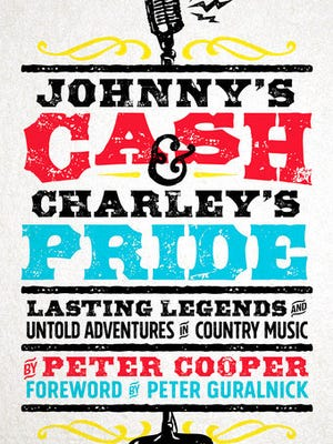 """This cover image released by Spring House Press shows """"Johnny's Cash & Charley's Pride: Lasting Legends and Untold Adventures in Country Music"""" by Peter Cooper."""