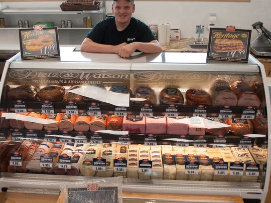 Assistant manager Sam Heritage stands behind the deli counter at the new Heritage's Dairy Store in  West Deptford.
