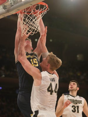 Michigan center Jon Teske dunks over Purdue center Isaac Haas during second half action of the Big Ten Tournament  Championship game Sunday, March 4, 2018 at Madison Square Garden in New York.