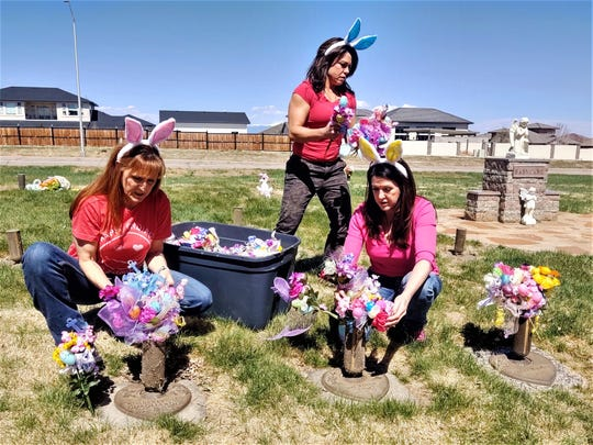 DeAn Dickinson, right, together with friends Cindy Poole, left, and Lori Santilli-Green, center, brighten up the graves of children buried at Babyland, in the Imperial Memorial Gardens cemetery. Pueblo Chieftain photo