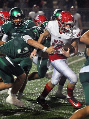 Holliday's Kade Patterson (12) runs up the middle against Iowa Park as defensive end Joe Bever (30) slows him down Friday night at Hawk Stadium in Iowa Park.