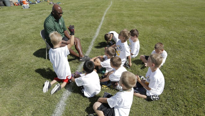 Green Bay Packer Alumni Harry Sydney talked to the campers after signing autographs during a question and answer session.  Green Bay Packers Youth Football Summer Camp is spending a week in Oshkosh at the 20th Avenue YMCA.  Each day a Packer alumni spends the day with the campers as they go over drills and provide a safe, non-contact football instruction for children 6 to 14 years old.  The camp is led by USA Football certified coaches where they learn to run, throw, catch, defend, work on football skills and develop life skills.