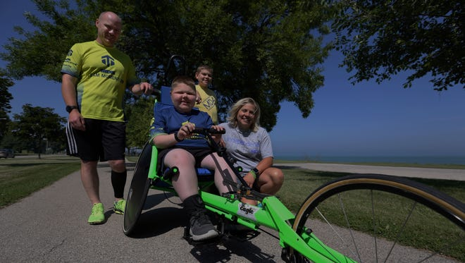 Devin Argall, 14, who has Muscular Dystrophy, poses for a photo with his father, Josh, half-brother, Daniel Kaufmann, and mother Dawn Kaufmann at the Mariners Trail on Wednesday, July 20. The family customized the steering wheel so Devin could have more fun during the running.