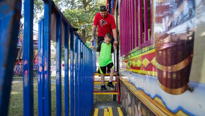 Alexander Haar, 8, and his dad Robert Haar exit the Fun House at the Special Kids Day at Fall Fest on Tuesday morning.