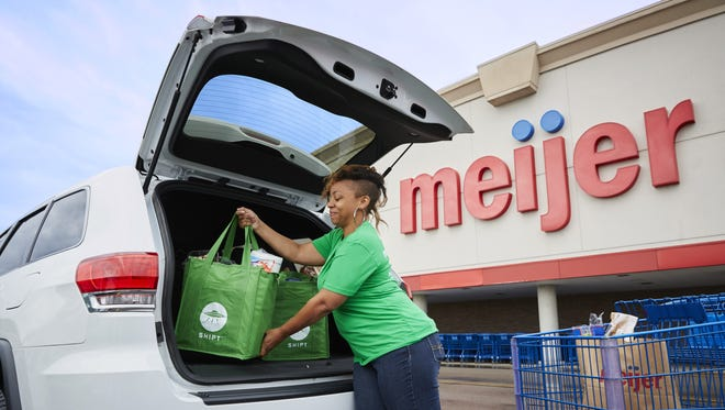 A Shipt personal shopper loads up a car full of Meijer groceries before a delivery.