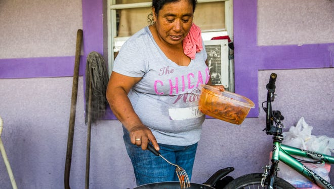 Macrina Cruz cooks the last of her family's food on a propane-heated portable stove in front of her Immokalee home on Tuesday, Sept. 12, 2017. Cruz's family evacuated before the storm and planned on buying more food there, but many stores were out or had raised their prices. Since Immokalee lost power when Hurricane Irma hit on Sunday, people have lost the food in their refrigerators and have not been able to cook what is left. Many families didn't stock up on nonperishables before the hurricane, as it is advised, because they didn't have the extra funds or because stores ran out.