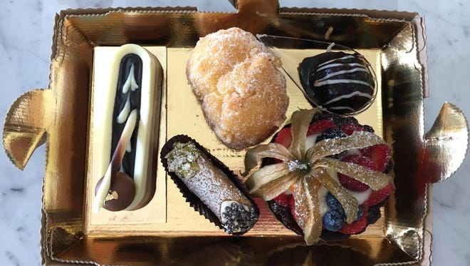 A to-go box of pastries awaits its lid at the Moorpark location of Carrara Pastries, one of more than 35 area food and beverage purveyors participating in the Ventura County Star Food & Wine Experience in Ventura on Oct. 1. Pictured from left: gluten-free Trilogia, a ricotta-filled cannoli, a frittelle, a vegan fruit tart and a bite-size profitterole.