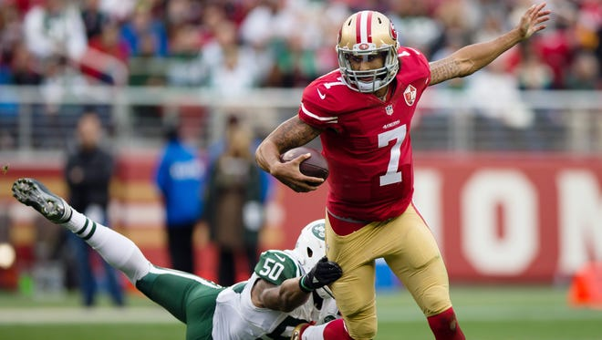49ers quarterback Colin Kaepernick tries to run while Jets outside linebacker Darron Lee grabs onto his pants during their game Sunday.