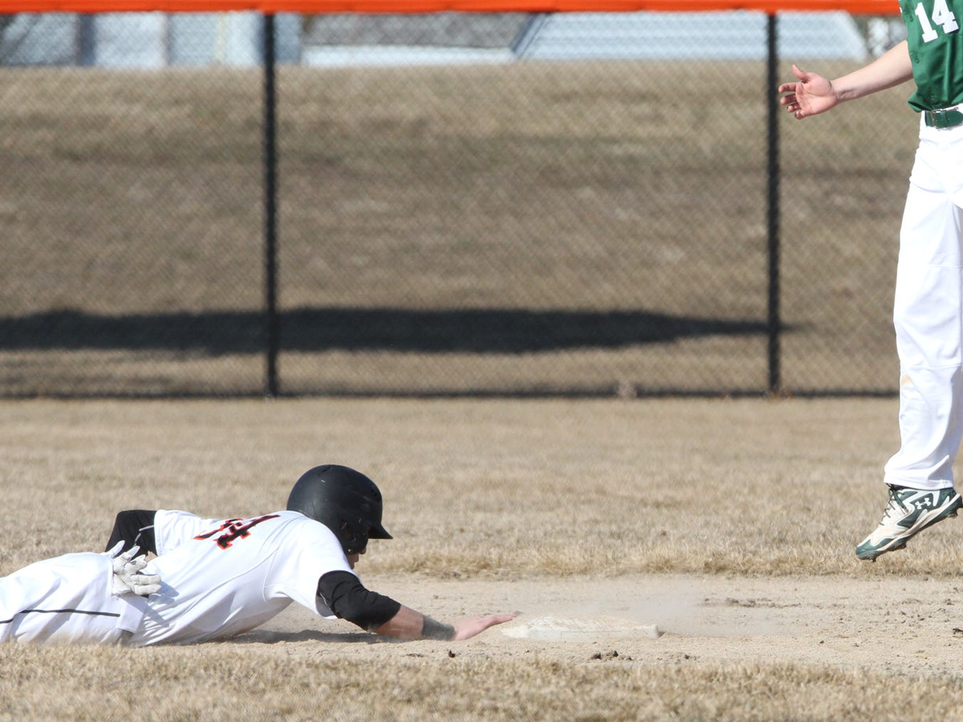 Brighton's Colin McClelland slides back to second base during the fourth inning in Wednesday's opener. He drove in the first run of the game for the Bulldogs in both games as Brighton earned a sweep.