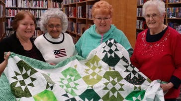 LAUGH members Benita Fish, left, Dee Sherman, Lois Green and founder Joyce Griffith show one of their quilted projects.