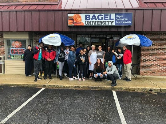 A day of service for students and staff from Cunningham Academy included cleaning up store fronts and windows, picking up trash and cleaning inside some area businesses.