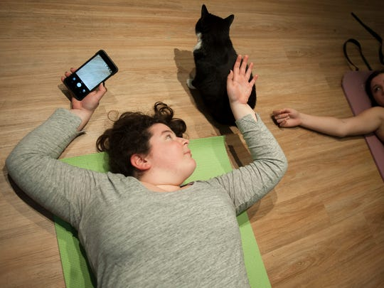 Manayunk resident Kristi Farinelli, left, pets a cat as Manayunk resident Sarah Greenberg looks on during a yoga class at  Le Cat Cafe in Philadelphia.
