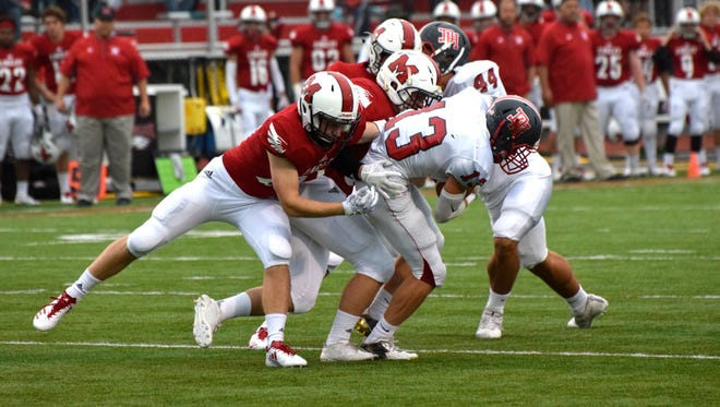 The Milford defense wraps up Dixie Heights' Dylan Sears (13) after a short gain.
