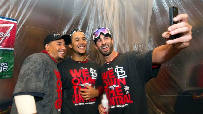 From left, Rafael Furcal, Jon Jay and Daniel Descalso celebrate the Cardinals' division title.
