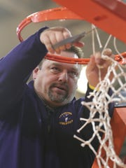 Lexington's Scott Hamilton cuts the net after the regional