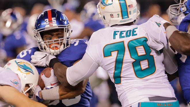 New York Giants running back Marshaun Coprich (35) is grabbed by Miami Dolphins defensive end Terrence Fede (78) during the fourth quarter of a preseason NFL football game, Friday, Aug. 12, 2016, in East Rutherford, N.J. (AP Photo/Ray Stubblebine)