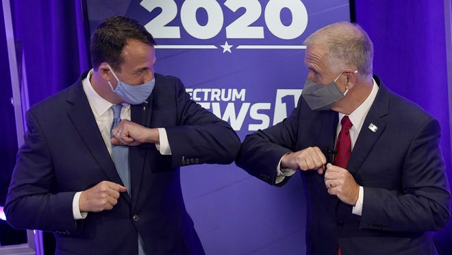 Democratic challenger Cal Cunningham, left, and  U.S. Sen. Thom Tillis, R-N.C. greet each other after a televised debate Thursday, Oct. 1 in Raleigh, N.C.