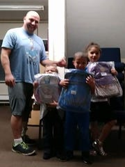 Paul Hulse of HAVEN/Beat the Street with three of the Swain siblings -- Jonniana, Corey and Kiana -- and their new school backpacks donated by Asbury Park Press readers.