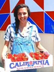 Megan Bunn, granddaughter of Chris Bunn, holds a flat of organic strawberries produced at The Farm.