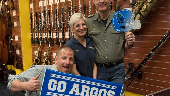 Steven, Nan and Jim DeStafney, owners of Blues Angel Music, show their support for the University of West Florida on Friday, May 4, 2018. The DeStafneys are hoping to work UWF to bring a marching band program to the university to help enhance the halftime experience during football games.