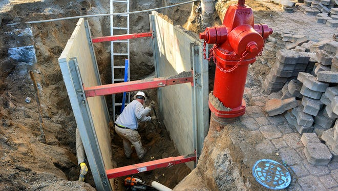 Brian Wurm of Molitor Excavating, St. Cloud, works deep beneath the sidewalk at Eighth Avenue and St. Germain Street on Monday.