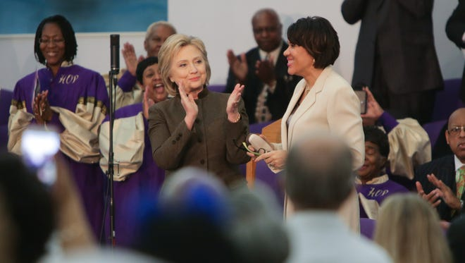 Democratic presidential candidate Hillary Clinton applauds Flint Mayor Karen Weaver (right) before speaking to Flint residents at the House of Prayer Missionary Baptist Church in Flint on Sunday February 7, 2016 about the Flint Water Crisis.