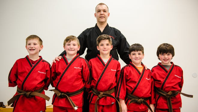 The Eichelberger brothers, from left, Travis, Matt, Zachary, Hunter, all 9, and Cody, 7, pose for a photo with their instructor and sensei Vince Fannon at Dubbs Karate Academy on May 13, 2016. On May 22 the five brothers are aiming to earn their junior black belts as well as a place in the book of Guinness World Records for the most brothers to earn a black belt on the same day.