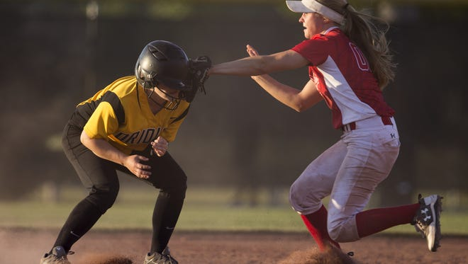Logan Shake of Avon High School is tagged out on a run-down between second and third by MacKenzie Dunlap of Crown Point. Crown Point won the  4A softball title game on Saturday, 2-1.
