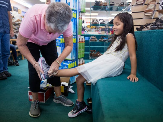 Vi Steffan, a volunteer and the first vice president of the Laces of Love board, helps Mirayah Rodriguez, 5, from the Guadalupe Center in Immokalee, get fitted for a free new pair of shoes at Snyderman's Shoes of Naples on Monday, July 17, 2017. The store has been sponsoring this event for over 20 years and is expecting around 250 kids throughout the week to get their new shoes.