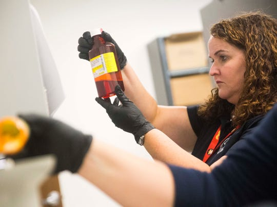 Manager of the medico-legal death investigation department Robin Slattery inspects a bottle of confiscated liquid oxycodone in the evidence room as medico-legal death investigator  Morgan Seymour counts pills in the Knox County Regional Forensics Center on Thursday July 13, 2017. The pills are eventually turned over to Knoxville Police Department to be destroyed.