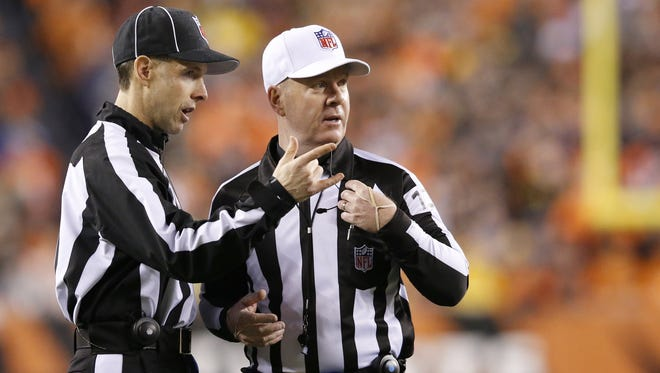 Referee John Parry (132), right, talks with an official in the during the NFL AFC wild-card game between the Pittsburgh Steelers and the Cincinnati Bengals, Saturday, Jan. 9, 2016, at Paul Brown Stadium in Cincinnati. The Steelers lead 6-0 at halftime.