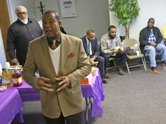 """The Rev. Ty Johnson, a pastor and founder of Churches Take a Corner, speaks at an event in Wilmington about violence and vandalism in the northeast part of the city. """"We speak to the trauma that our kids and our children are experiencing from gun violence in this neighborhood,"""" he said."""