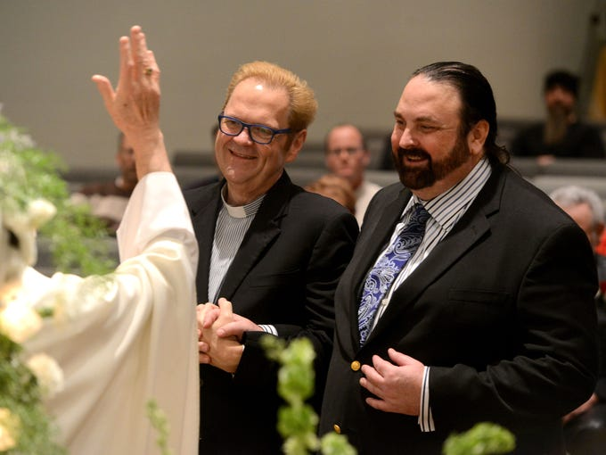 Rev. Jim Merritt, left, and Al Leach, are married by