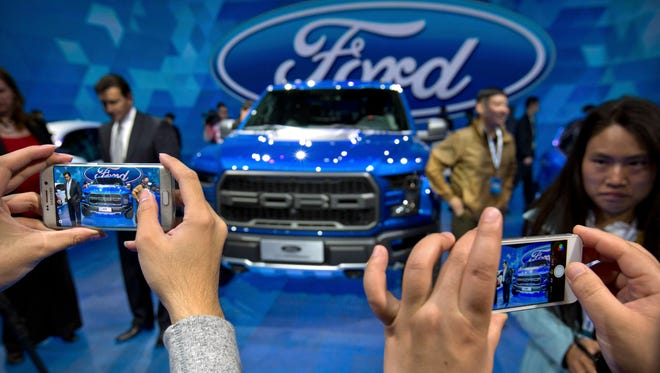 In this April 23, 2016, photo, attendees take smartphone photos at a promotional event for Ford Motor Company ahead of the Auto China car show in Beijing. Ford Motor Co. announced an agreement Tuesday, Aug. 22, 2017 with a Chinese partner to look into forming a joint venture to develop and manufacture electric cars in China. (AP Photo/Mark Schiefelbein)