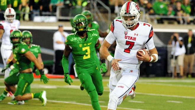 UTah QB Travis Wilson cruise in for a third-quarter touchdown in front of Oregon safety Tyree Robinson as the Utes pulled away from the Ducks in a blowout win.